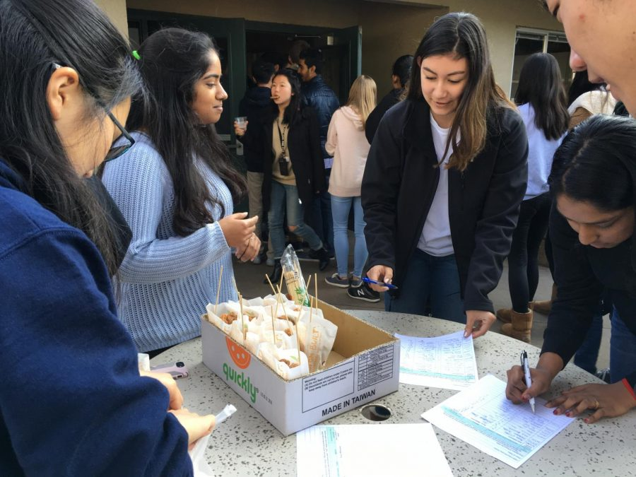 Megan Cardosi (12) and Neha Premkumar (11) buy from Harker Horizon members outside Manzanita during lunch on Friday. The research journal held its club week this week, fundraising for their costs of print publication and inDesign licenses.