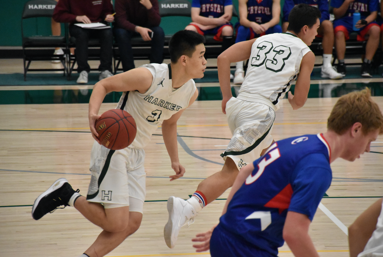 Junior Gene Wang dribbles across the court in the home game against Crystal Springs Uplands. They won the game by a margin of 36 points.