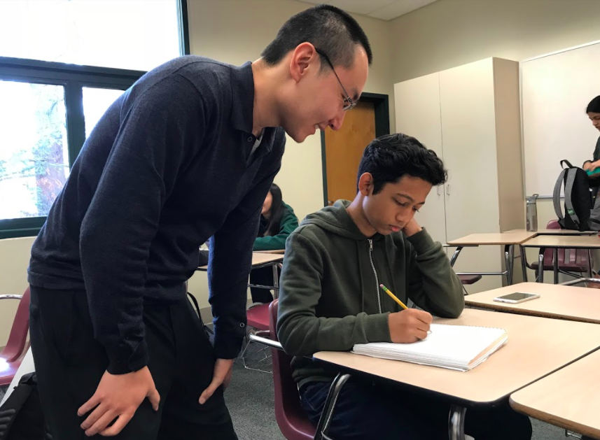Math teacher Yanxin Shi works with a student during class. Shi began teaching classes in January.