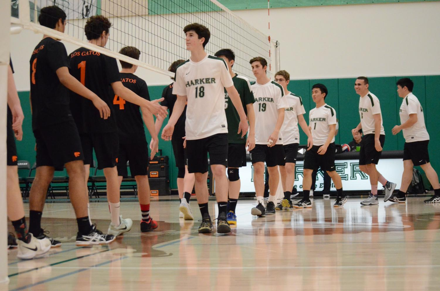 Before the game against Los Gatos High School, the boys volleyball team high fives their opponents. This was the first boys volleyball match played in the new Athletics Center.
