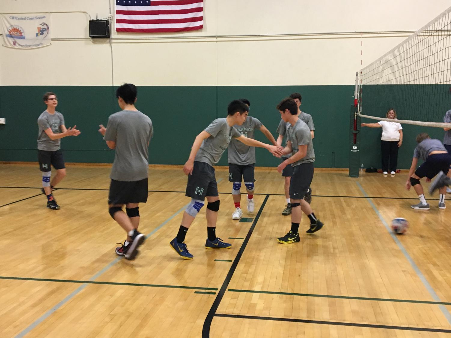 Members of the boys varsity volleyball team come together after a point. Bellarmine was the first team the boys played this season