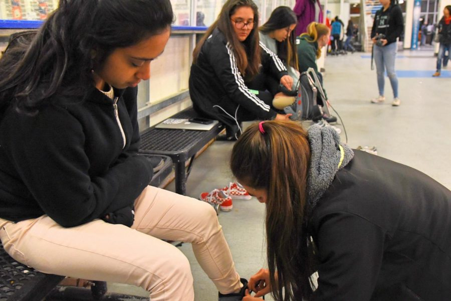 Cas Ruedy (10) helps Divija Bhimaraju (12) lace up her skates at the benches by the rink. Todays ice skating trip was open to all students.