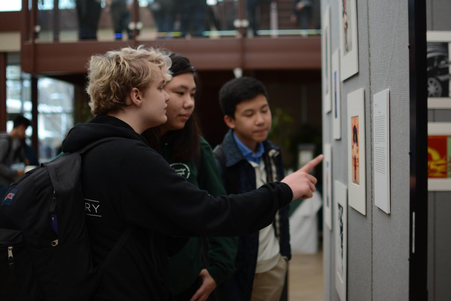 Students discuss art pieces displayed in Nichols Atrium. The works of this year's AP Studio Art students were featured in an exhibit up earlier this year.