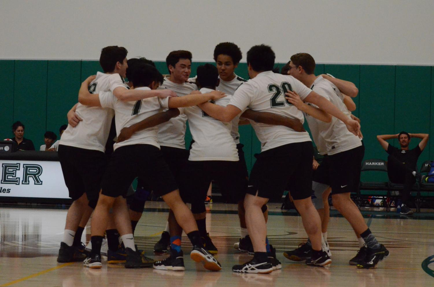 Between sets, the varsity boys volleyball team cheers within their huddle. They beat Cupertino High School in three sets.