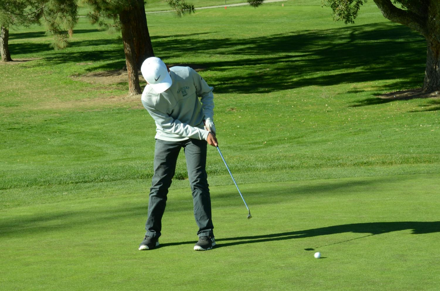 Gabe Yang (9) putts a golf ball across the San Jose Country Club's golf course. The boys' golf team played and defeated Nueva and Crystal Springs, keeping their undefeated streak of 6-0.