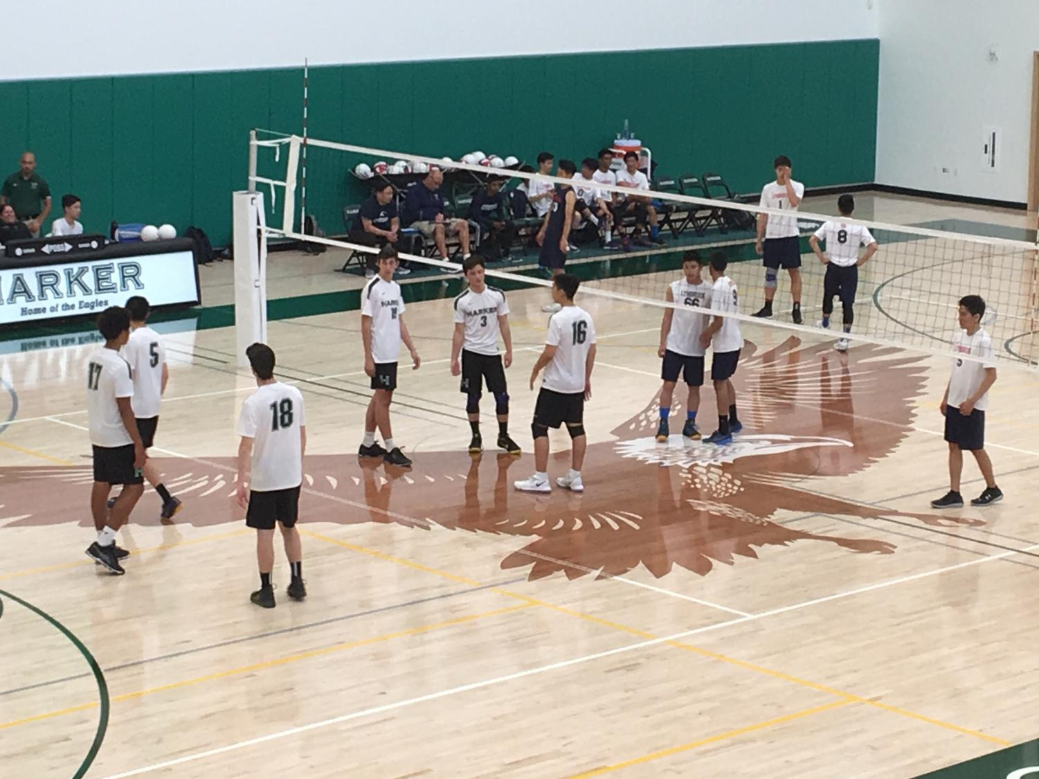 The varsity boys' volleyball game stands in position before the ball is served by the other team. They won their game against Lynbrook in three sets.