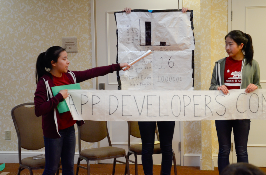 Tiffany Wong (11) gestures to a bar graph outlining the differences in duration of time required to resolve a cloud storage data breach between companies with security software EscapeBreach and those without. Tiffany, Taylor Lam (11), Sara Min (11) and Kelly Shen (11) placed first in the Senior Division Presentation of Action Plan with their skit.