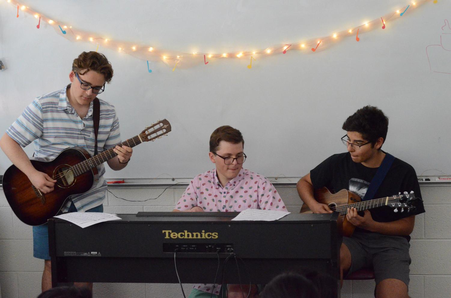 William Rainow (10), Thomas Rainow (10) and Joshua Valluru (10) play a Brazilian song together across their instruments. The Music Around the World showcase was held in English teacher Christopher Hurshman's room on April 24.