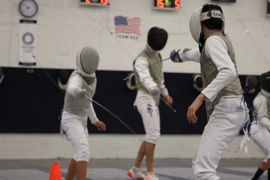Ethan (right) faces off against another fencer at practice. A fencing bout in foil occurs in three rounds of three minutes each, with victory being awarded to the first person to reach 15 points.