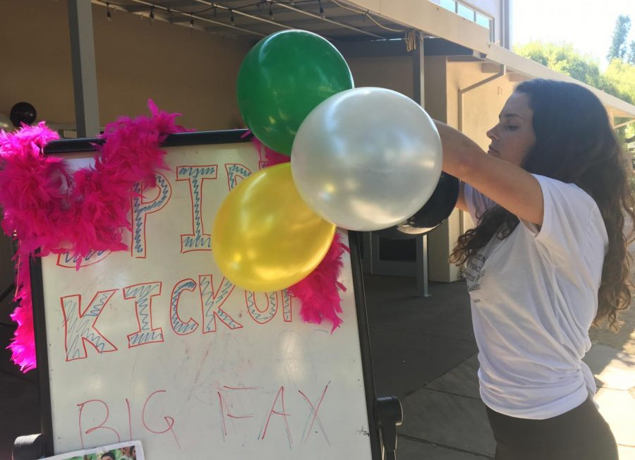 A student attaches balloons of the four class colors—yellow, black, white and green—to a sign advertising Spirit Kickoff in the auxiliary gym.