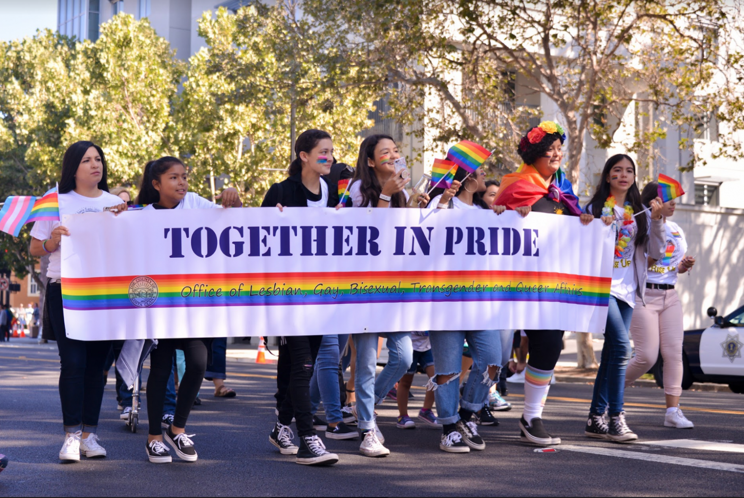 Student marchers representing the Office of LBTQ+ rights carry a festive banner in honor of Pride.