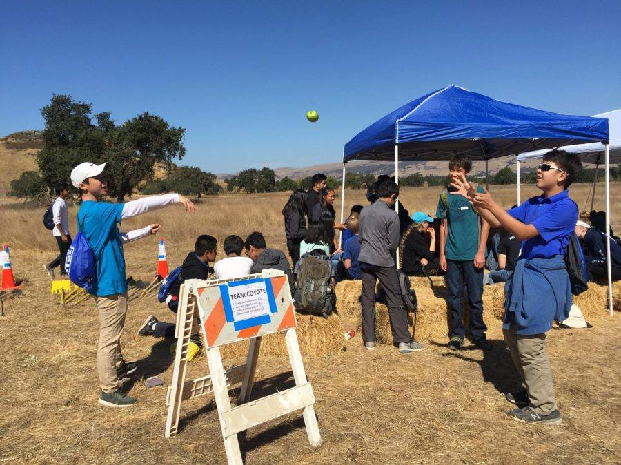 William Chien (9) and Spencer Cha (9) play catch with an apple while Jay Thilking (9) watches. The freshmen had some time to relax during their lunch break on their community service trip.
