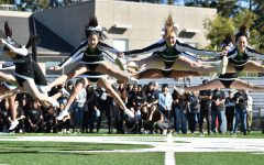 Cheerleaders leap in the air during their routine. After their performance, the classes competed in a scream-off.