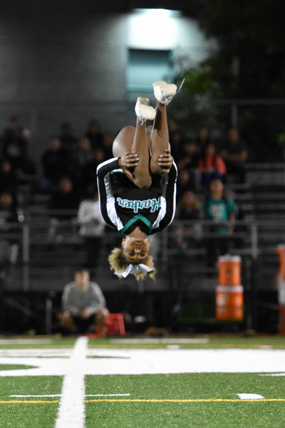 Lilly Anderson (12) performs a flip during a halftime cheer performance during the homecoming game. Cheer held their senior night yesterday at 6:45 before the home football game against Oakland Military Institute.