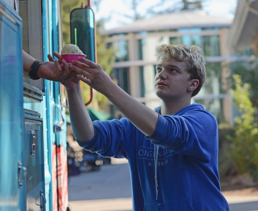 Evan Bourke (10) buys ice cream in a cup from the Twisted Chill ice cream truck after school today. Lines wrapped around the truck in the first few minutes after school.