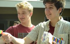 """Raphael Sanche (12) and Evan Bourke (10) hand out rainbow smiley face stickers on behalf of GSA club during lunch. """"As an ally of our young people who are coming along the process, it means that I get to witness firsthand the growth within our own student body as they're moving forward and understanding themselves and embracing themselves and being more public with who they are,"""