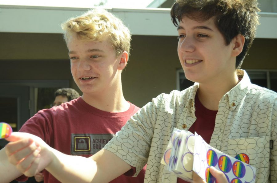 "Raphael Sanche (12) and Evan Bourke (10) hand out rainbow smiley face stickers on behalf of GSA club during lunch. ""As an ally of our young people who are coming along the process, it means that I get to witness firsthand the growth within our own student body as they're moving forward and understanding themselves and embracing themselves and being more public with who they are,"