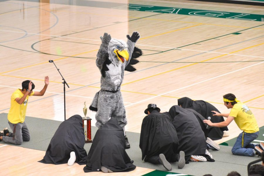 Members of the spirit team bow down to the eagle at the school meeting on Sep. 26. This new eagle costume is a recent addition to the upper school spirit arsenal, concurrent with the opening of the athletic center in September 2017.