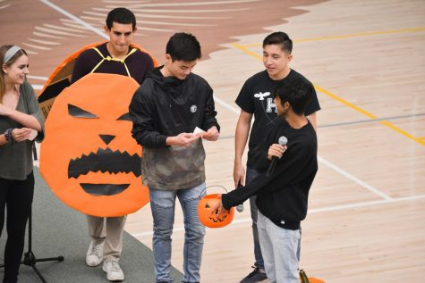 Junior spirit representative Vance Hirota (10) picks a number from a basket to draw for a pumpkin in preparation for a pumpkin carving competition later this week.