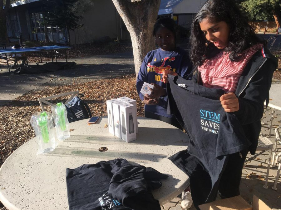 Suman Mohanty (10) holds up a STEM saves the worldt-shirt at the WiSTEM club week booth outside Manzanita. WiSTEM had  speakers, a movie screening, and fundraisers for education for girls in Kenya during its club week.