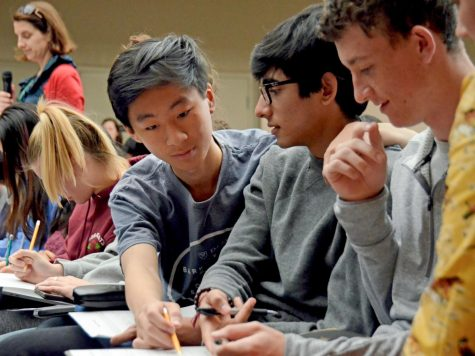 Andy Lu (10) helps Arjun Virmani (10) with his worksheet during the sophomore LIFE assembly on Nov. 6. The students filled out worksheets during the assembly with information about their courses, how much time they allocated to them weekly and how much they enjoyed them.