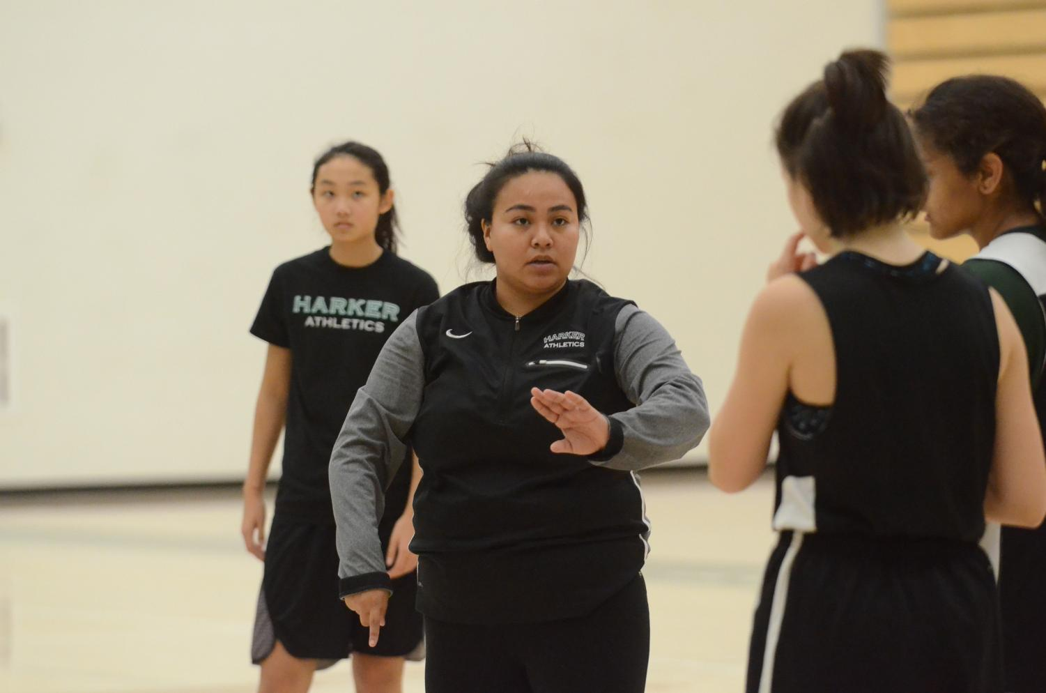 Head coach Daniza Rodriguez talks to players during a girls basketball practice.