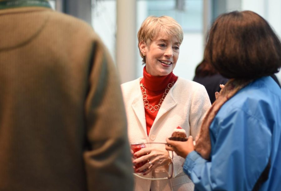 Sue Smith, who has worked as an archivist, a librarian and the K-12 Library Director at The Harker School, talks with colleagues at her retirement party this afternoon in the Nichols Rotunda.