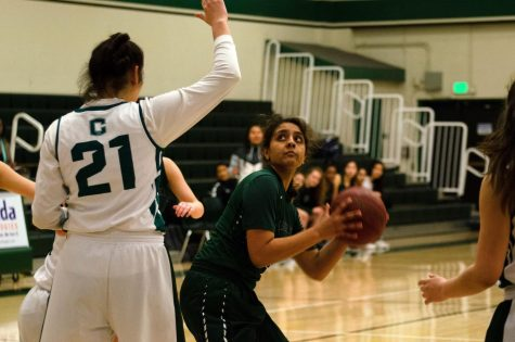 Varsity girls basketball captain Akhila Ramgiri (12) tries to score over a James Lick defender. The girls end their season with an overall record of 13-10.