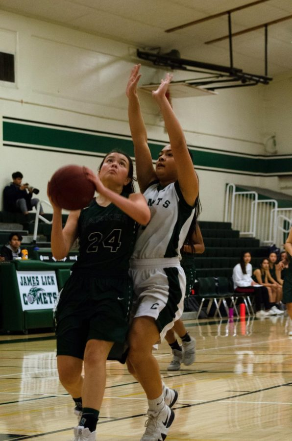 Varsity+captain+Sara+Lynn+Sullivan+%2811%29+attempts+to+score+in+a+paint+as+a+James+Lick+player+closely+guards+her.+The+varsity+boys+finished+their+season+with+an+overall+record+of+11-14.+