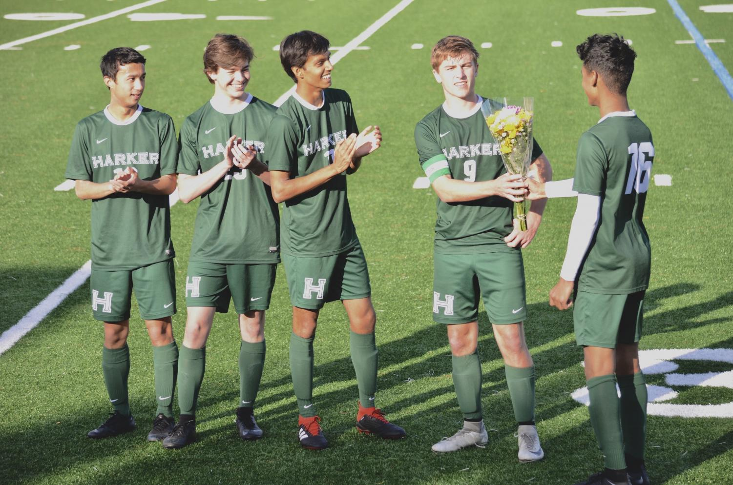 Shomrik Mondal (11) hands a bouquet to varsity captain Jared Anderson during the halftime senior recognition ceremony. The ceremony honored Edwin Su, Jack Dawson, Krish Kapadia and Jared.