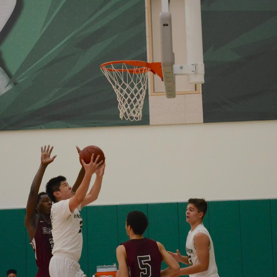 Eric Zhu (10) scores in the paint. The varsity boys face off at Menlo at 6:30 p.m. on Tuesday, and celebrate their senior night at home against Pinewood on Feb. 12. at 6:30 p.m.