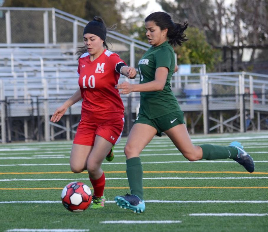 Varsity captain and senior Ria Gupta chases down a Mercy player during the senior night game.