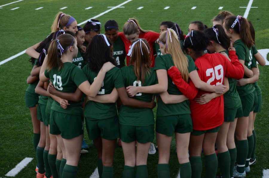 The girls soccer team huddles together during their Kicks Against Cancer game. Both the girls and boys soccer team placed third, while the boys basketball team placed first for their respective CCS Scholastic Awards.