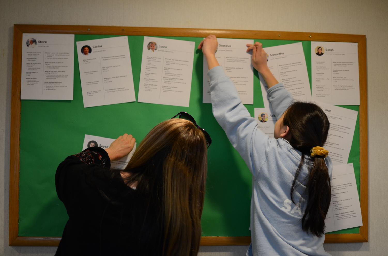 Director of Community Service Kerry Enzensperger and Alyssa Huang (11) position the posters. LIFE agreed to lend their bulletin board to the Appreciation Committee.