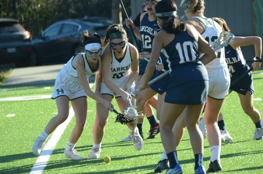 Zoe+Sanders+%2810%29+and+Callie+Mayer+%289%29+look+to+pick+up+the+ground+ball+during+the+lacrosse+team%E2%80%99s+game+against+Lincoln+High+School+on+Wednesday%2C+Mar+13.+The+girls+currently+maintains+an+overall+record+of+3-2.