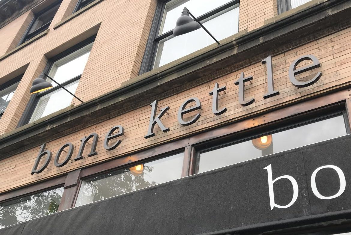 In lowercase serif font, Bone Kettle's simple yet modern sign hangs in front of the restaurant. The eatery is located on 67 N Raymond Ave in Old Town Pasadena nearby the California Institute of Technology and the Metro Gold Line.