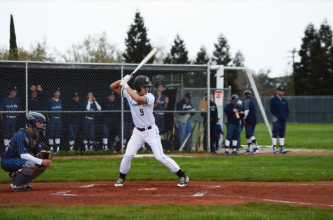 Trevor Thompson (12) steps up to bat, preparing for the pitch to be thrown. Despite their Friday game being cancelled, the Eagles still played well during the match, with strategic hits from freshman Bobby Wang and senior Zachary Hoffman and a dive for home base by junior Max Lee.
