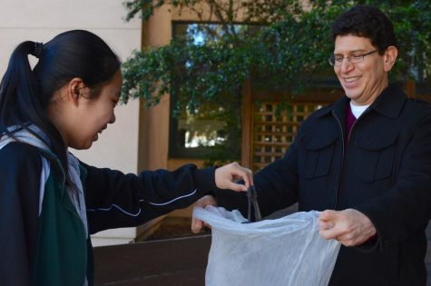 During the campus clean-up on Friday, Clarice Wang (9) put a piece of trash in a garbage bag held open by Abel Olivas, Spanish teacher and department head of Modern and Classical languages.