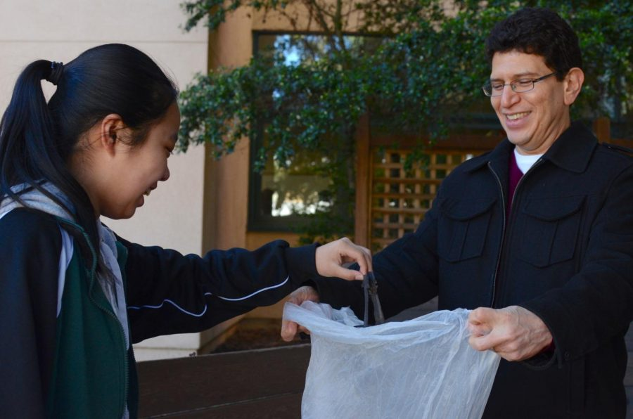 During+the+campus+clean-up+on+Friday%2C+Clarice+Wang+%289%29+put+a+piece+of+trash+in+a+garbage+bag+held+open+by+Abel+Olivas%2C+Spanish+teacher+and+department+head+of+Modern+and+Classical+languages.