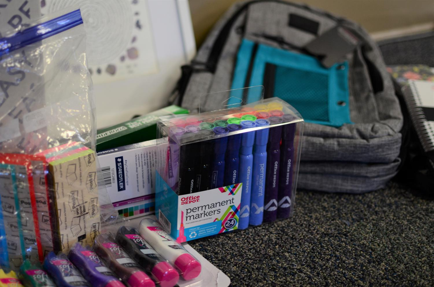 A gray backpack, markers, and other miscellaneous school supplies sit in the corner of upper school math teacher Bradley Stoll's classroom. The contents of each donated backpack usually vary depending on the items and quantity of items that are donated.