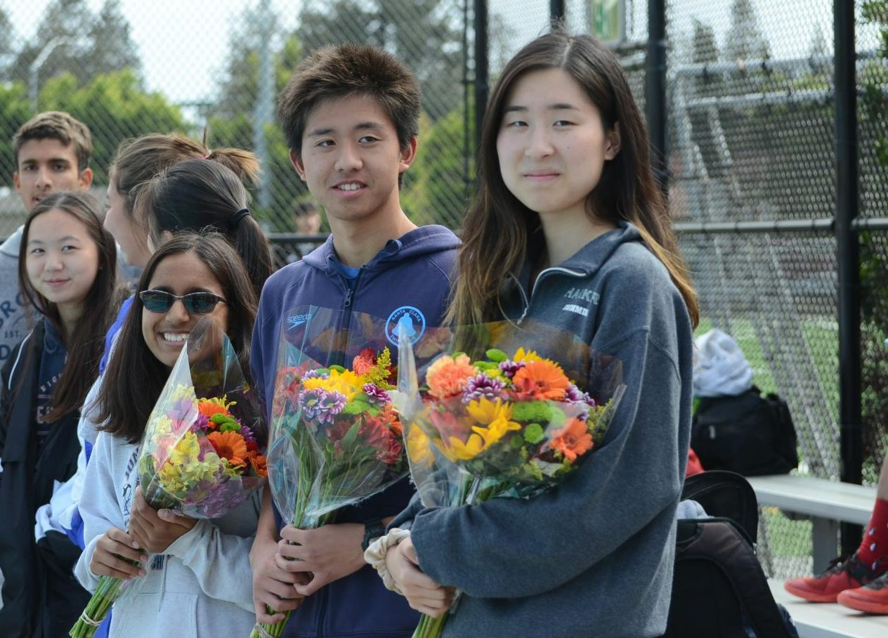 "Ihita, Alex and Angela hold bouquets ahead of the meet. ""This is their last event with our school, and it's kind of sad to think about, so we'd like to end it with a joyous festival to honor all of them,"" Cassandra Ruedy (11) said."