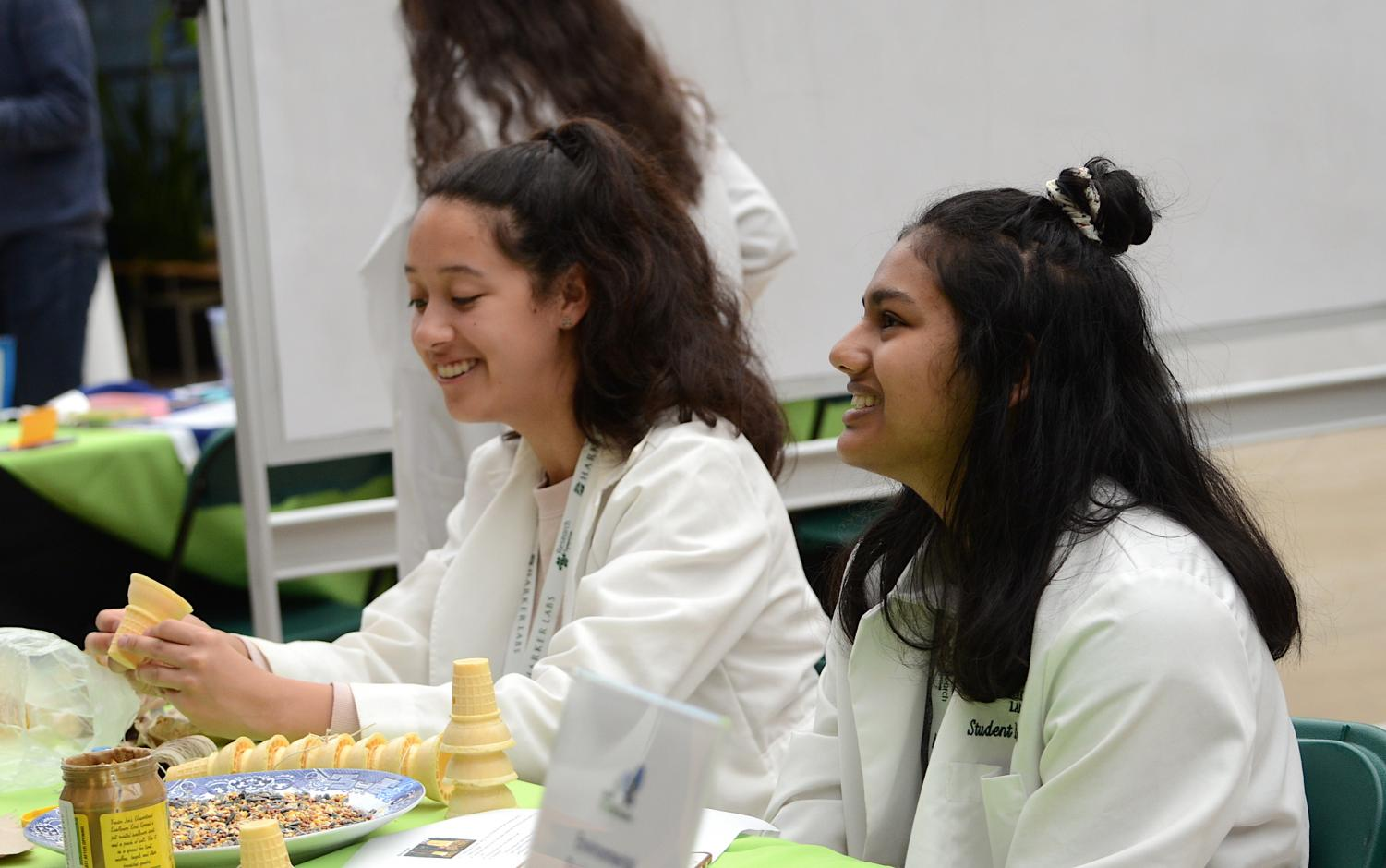 WiSTEM volunteers Emma Dionne (10) and Vidya Jeyendran (10) lead one of the tables for WiSTEM's food-based modeling activity. The symposium's scheduled events included exhibit tables, keynote speakers, student and alumni panels, poster presentations and a variety of other activities and workshops.