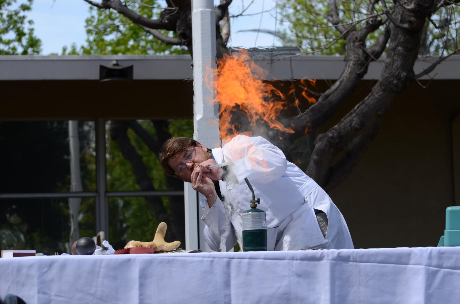 Upper+school+chemistry+teacher+Andrew+Irvine+blows+a+powder+above+a+flame+to+create+a+burst+of+fire.+The+annual+chemistry+%22magic+show%22+is+one+of+the+symposium%27s+most+beloved+traditions.