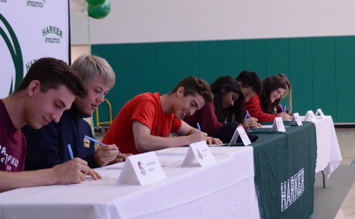 The seniors, sitting at a long table with name tags featuring their name, sport and college, sign their letters of commitment to play in college. Signing day was held in the athletics center during long lunch at 12:45 on Thursday, April 18.