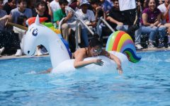 Katie Li (10) pulls herself up onto the inflatable unicorn float during today's regatta race. Katie's class, the sophomores, won the race, followed by the freshmen in second and the seniors and juniors in third.