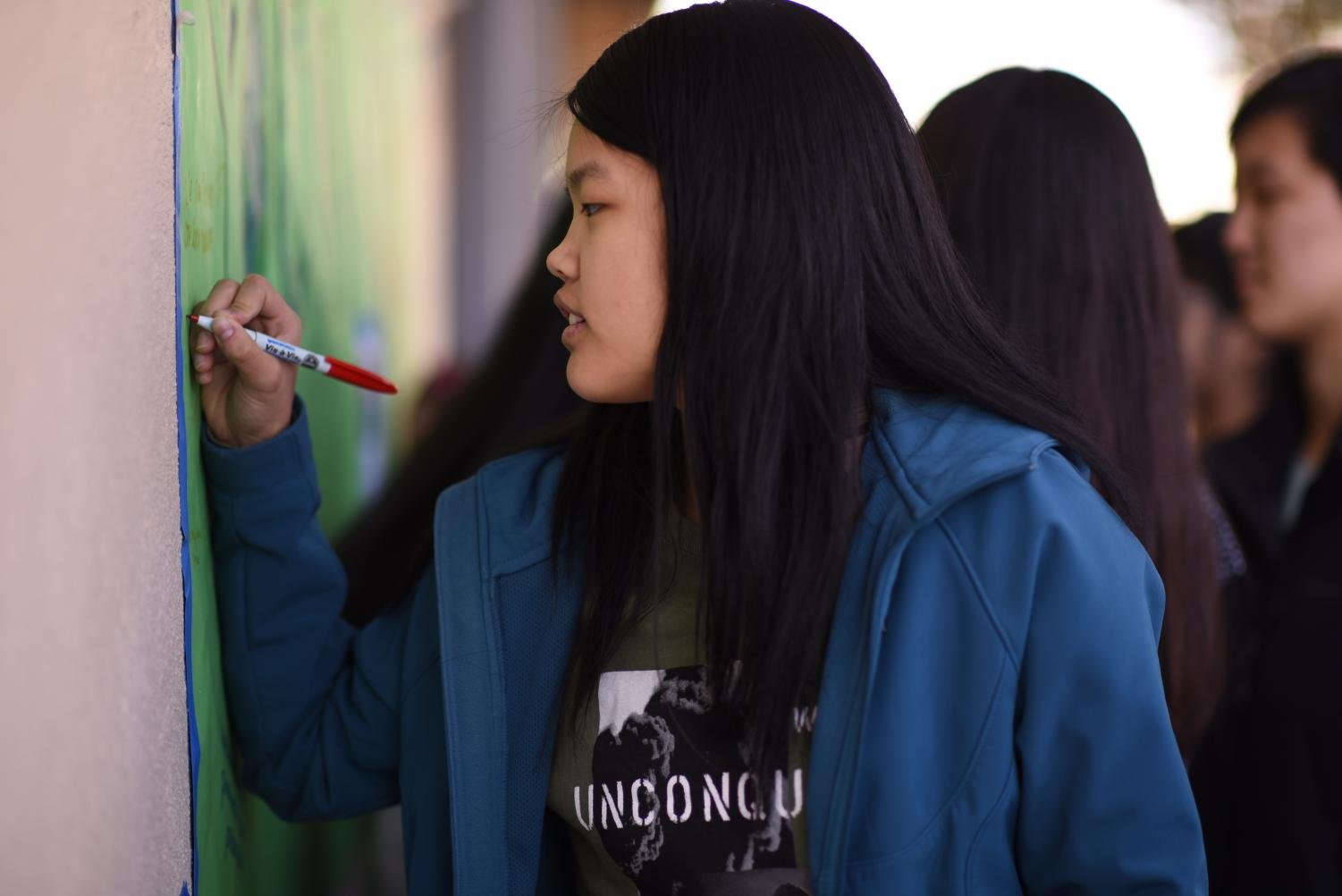 Helen+Yang+%2812%29+writes+a+message+on+a+banner+with+student+ideas+on+helping+the+planet.+Students%2C+who+were+encouraged+to+wear+green+or+blue%2C+had+the+chance+to+write+messages+on+posters+and+sign+petitions+during+the+rally.