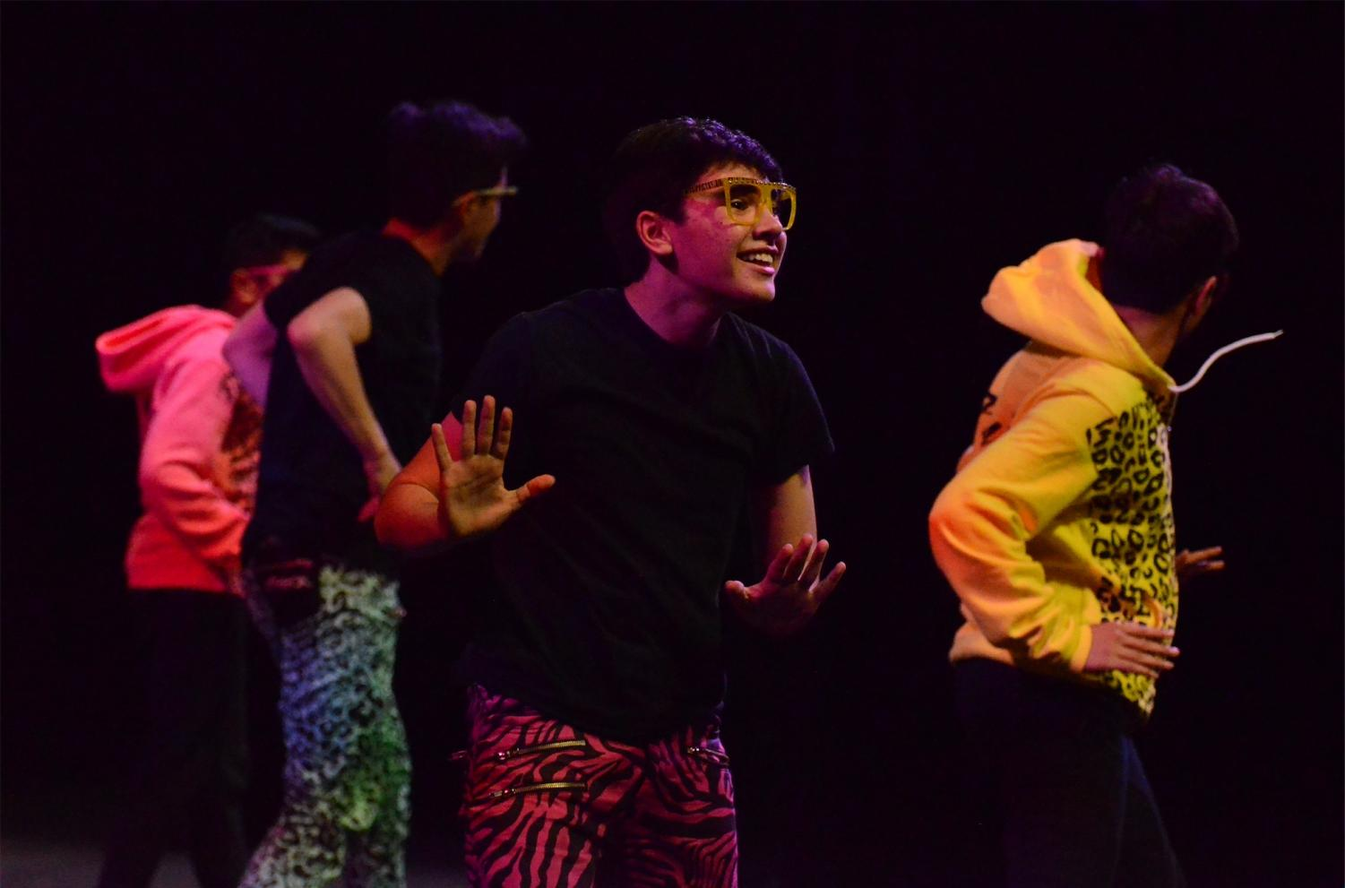 Joel Morel (11) grins at the audience as he dances in perfect coordination with his fellow members of Kinetic Krew. Kinetic Krew,  an all-boys group directed by Rachelle Haun, features dancers from 9th to 12th grade.