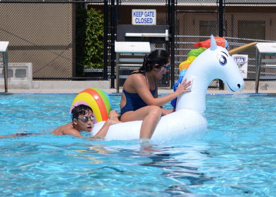Ethan+Hu+%2811%29+pushes+Alicia+Xu+%2811%29+across+the+pool+as+she+sits+in+an+inflatable+unicorn.+In+the+Regatta%2C+each+grade+sported+a+team+of+four+students.+Two+at+a+time%2C+one+student+rode+the+inflatable+unicorn+while+the+other+pushed+the+float+from+behind%2C+then+switching+positions+and+swimming+to+the+other+side+of+the+pool.+