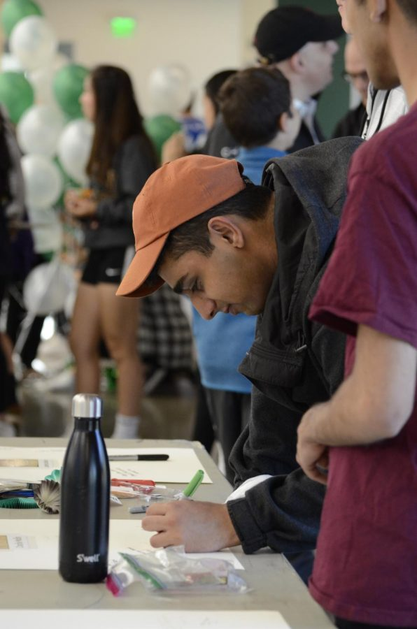 Abhinav Joshi (12) signs a senior poster. The crowd could enjoy food and sign posters in the athletic center before the match.