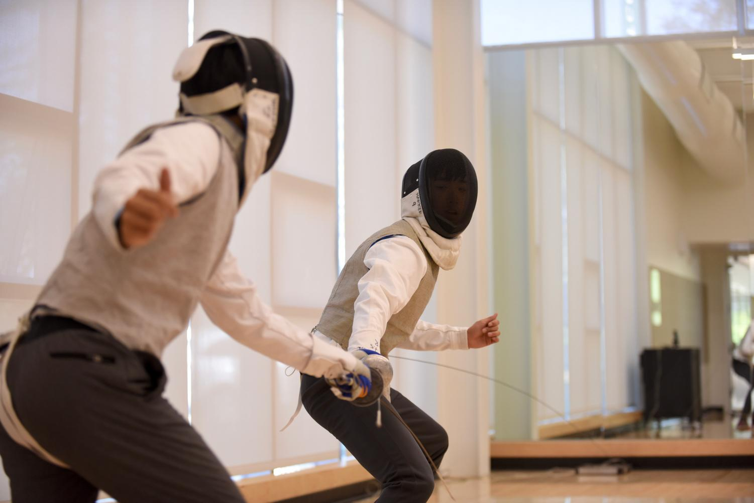 Two students practice fencing using the electric equipment, which is widely used in competitive fencing. The class was held on May 3.
